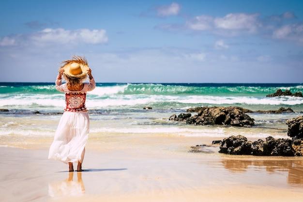 Jeune femme en robe blanche et chapeau au bord de la mer