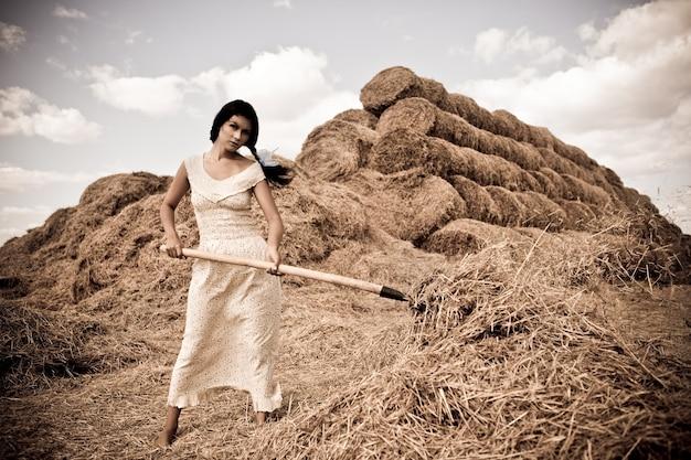Jeune femme en robe blanche debout avec une fourche à foin à la main dans le champ