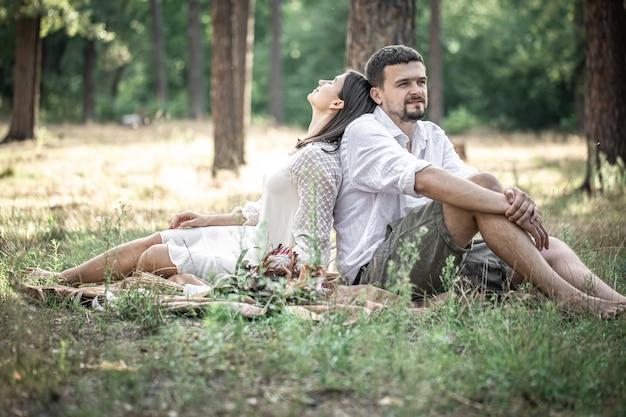 Une jeune femme en robe blanche et un homme en chemise sont assis dans la forêt sur l'herbe, un rendez-vous dans la nature, une romance dans le mariage.