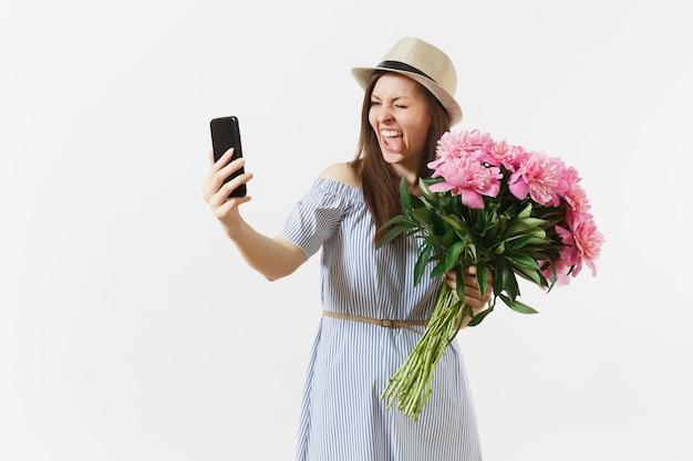 Jeune femme en robe bleue, chapeau tenant un bouquet de belles fleurs de pivoines roses, faisant selfie sur téléphone portable isolé sur fond blanc. saint-valentin, concept de vacances de la journée internationale de la femme.