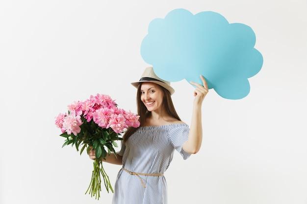 Jeune femme en robe bleue, chapeau tenant un nuage de parole vide vide, bulle de dialogue avec texte de lieu, bouquet de fleurs de pivoines roses isolées sur fond blanc. notion de vacances. espace de copie de la zone publicitaire.