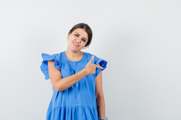 Jeune femme en robe bleue pointant sur le côté et à l'optimisme