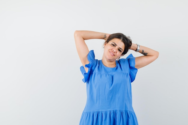 Jeune femme en robe bleue tenant les mains derrière la tête et l'air détendu
