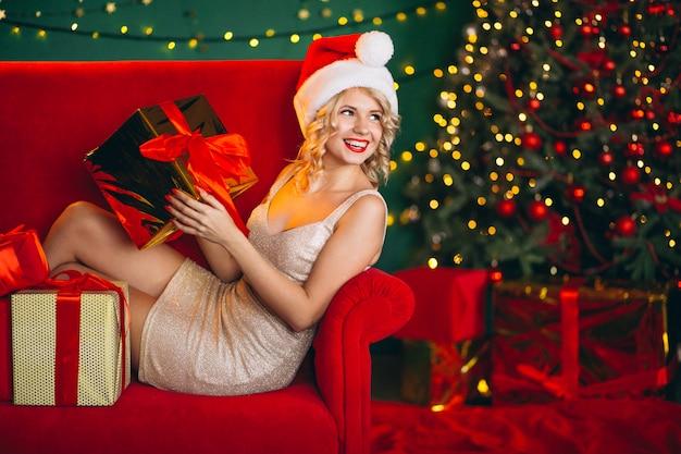 Jeune femme en robe avec des cadeaux de noël assis sur un canapé