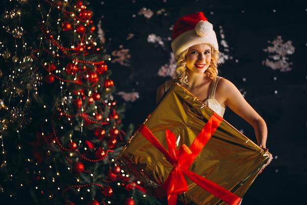 Jeune femme en robe avec des cadeaux de noël par sapin de noël