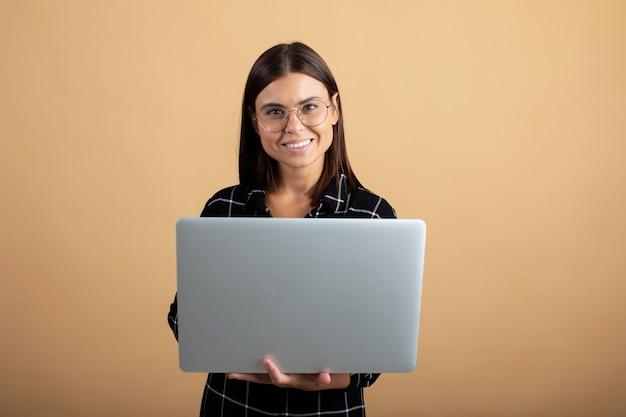 Une jeune femme en robe à carreaux se dresse sur une orange avec un ordinateur portable