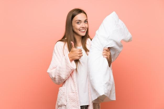 Jeune femme en robe de chambre sur un mur rose donnant un geste du pouce