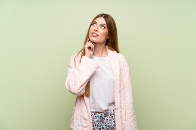 Jeune femme en robe de chambre sur le mur vert, pensant à une idée