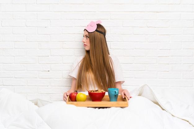 Jeune femme en robe de chambre avec petit déjeuner à la recherche de côté