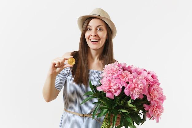 Jeune femme en robe, chapeau tenant bitcoin, pièce de couleur dorée, bouquet de belles fleurs de pivoines roses isolées sur fond blanc. affaires, livraison, achats en ligne, concept de monnaie virtuelle.