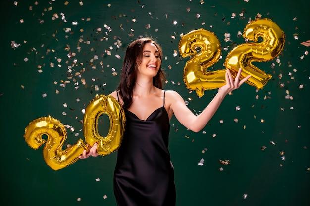 Jeune femme en robe de cocktail célébrant le nouvel an et tenant des ballons dorés
