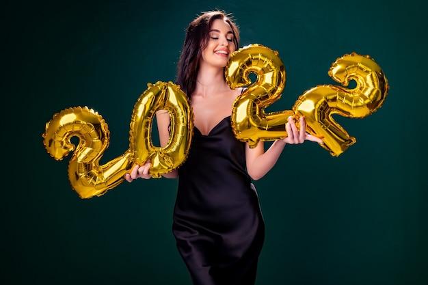 Jeune femme en robe de cocktail avec un maquillage lumineux célébrant le nouvel an et tenant des ballons dorés ...