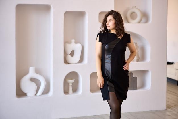 Jeune femme en robe de cuir se tient à l'intérieur