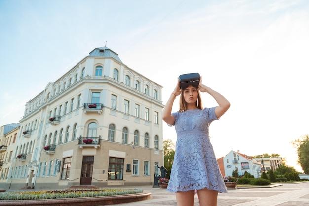 Jeune femme en robe d'été avec appareil vr en plein air.