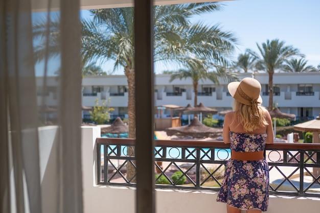 Jeune femme en robe d'été blanche regardant debout sur un balcon d'hôtel au coucher du soleil.