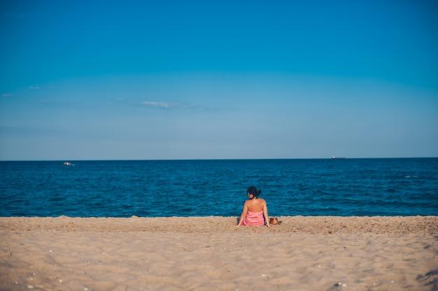 Jeune femme en robe d'été avec chapeau de paille à la recherche d'un ciel et de la mer