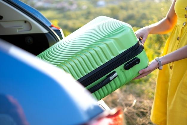 Jeune femme en robe d'été jaune prenant une valise verte du coffre de la voiture. concept de voyage et de vacances.