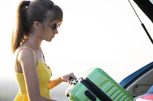 Jeune femme en robe d'été mettant une valise verte à l'intérieur de son coffre de voiture. concept de voyage et de vacances.