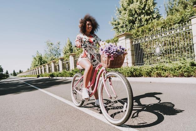 Jeune femme en robe à fleurs fait du vélo dehors.