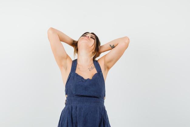 Jeune femme en robe gardant les mains derrière la tête en étirant les coudes et en ayant l'air détendu