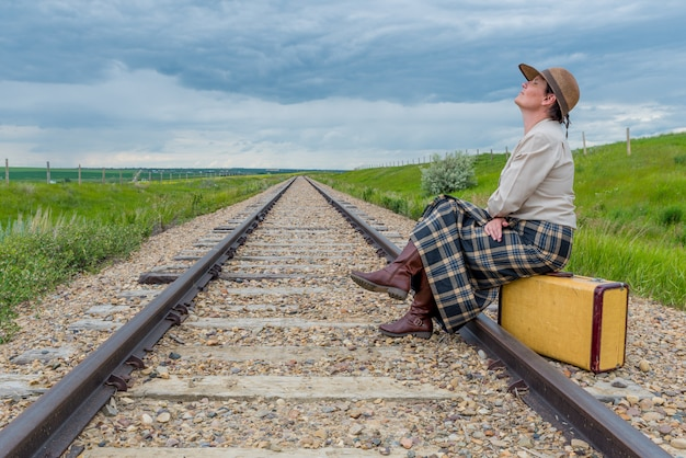 Jeune femme en robe historique assis sur une valise vintage sur voie ferrée avec tête en arrière et les yeux fermés-concept de voyage