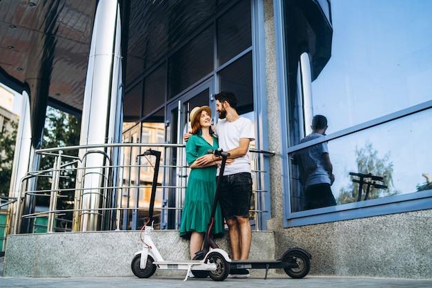 Une jeune femme en robe et un homme se parlent et profitent d'un moyen pratique de voyager en ville sur des scooters électriques