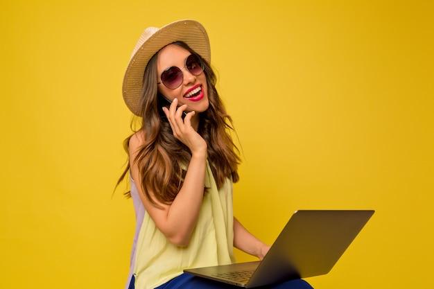 Jeune femme en robe jaune avec chapeau et lunettes de soleil écouter de la musique, parler au téléphone et à l'aide d'un ordinateur portable