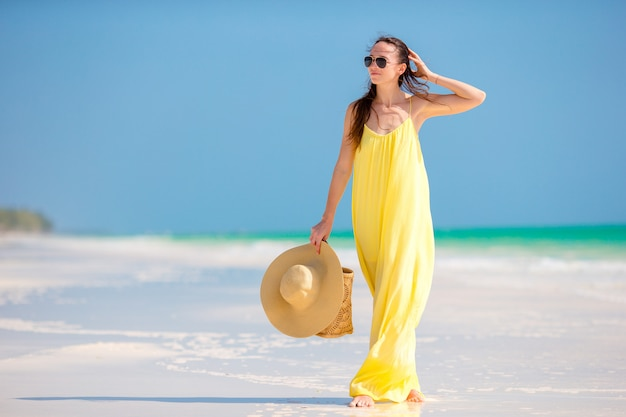 Jeune femme en robe jaune avec un chapeau pendant les vacances à la plage tropicale