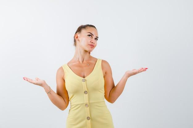 Jeune femme en robe jaune montrant un geste impuissant, levant et regardant pensif, vue de face.