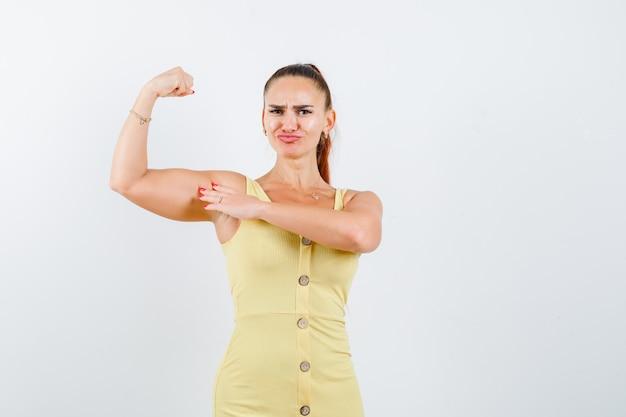 Jeune femme en robe jaune montrant les muscles du bras et l'air confiant, vue de face.