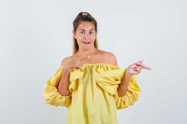 Jeune femme en robe jaune pointant vers le côté droit et regardant étonné, vue de face.