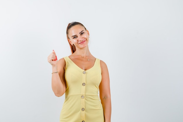 Jeune femme en robe jaune posant tout en levant la main et regardant jolly, vue de face.