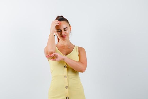 Jeune femme en robe jaune tenant la main sur la tête et regardant abattu, vue de face.