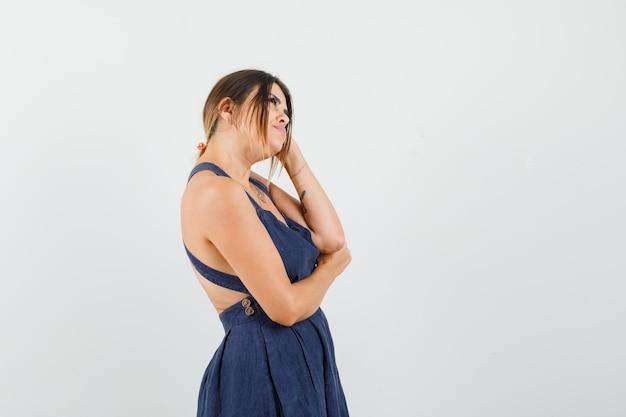 Jeune femme en robe en levant et regardant pensive.