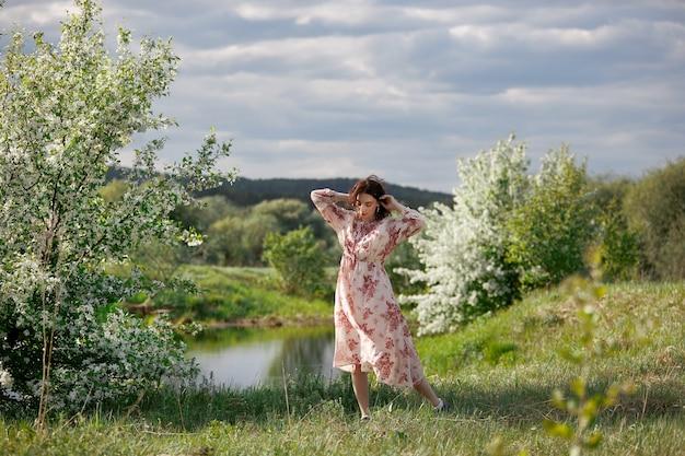 Jeune femme en robe longue se promène dans le jardin de printemps près du lac. la fille se repose dans la nature, le printemps est arrivé