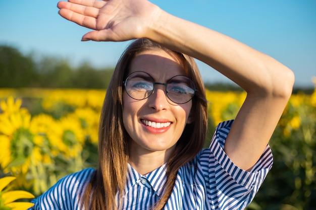 Jeune femme en robe et lunettes accueille le lever du soleil et se couvre le visage des rayons du soleil sur un champ de tournesol.