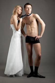 Jeune femme en robe de mariée debout, tenant l'homme en sous-vêtements par cravate