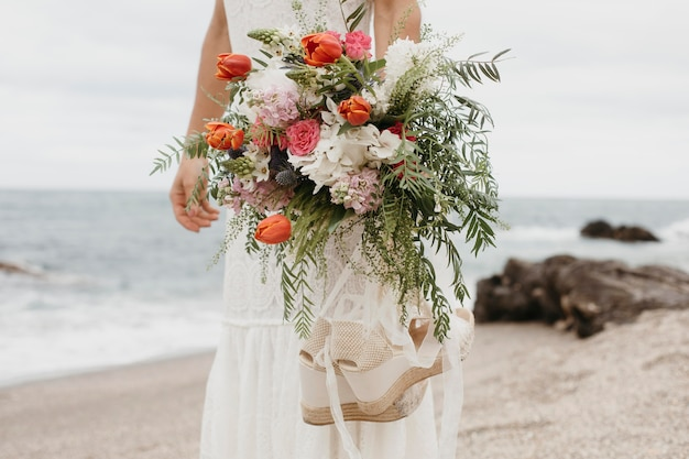 Jeune femme en robe de mariée à la plage