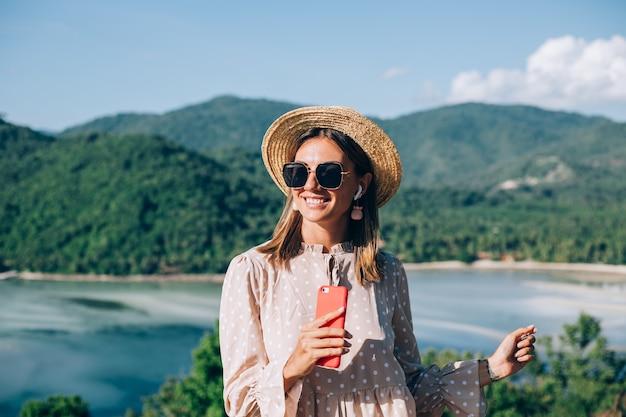 Jeune femme en robe mignonne d'été, chapeau de paille et lunettes de soleil dansant avec smartphone à portée de main