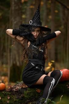 Jeune femme en robe noire avec chapeau de sorcière et citrouille orange placé autour de la forêt, concept d'halloween. thème de l'horreur.