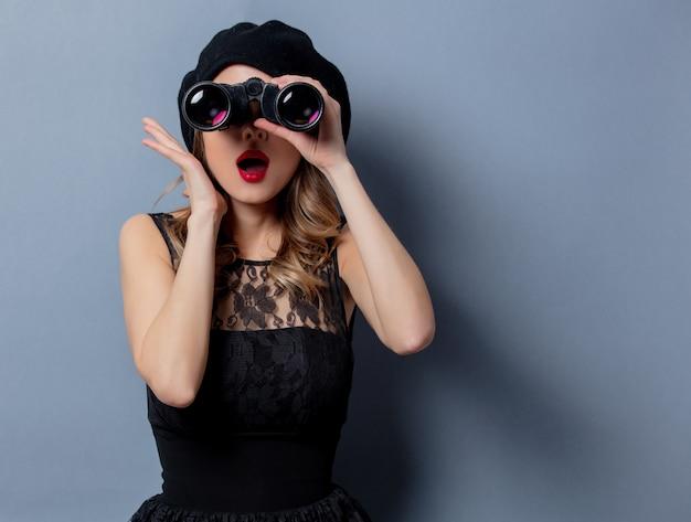 Jeune femme en robe noire avec des jumelles sur un mur gris