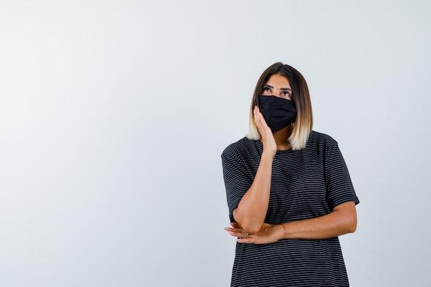 Jeune femme en robe noire, masque noir appuyé sur la joue sur la paume, pensant à quelque chose et à la vue pensive, de face.