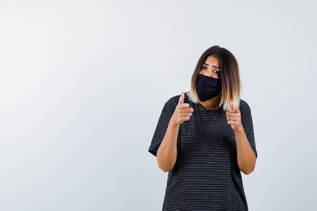 Jeune femme en robe noire, masque noir pointant vers la caméra avec l'index et à la grave, vue de face.