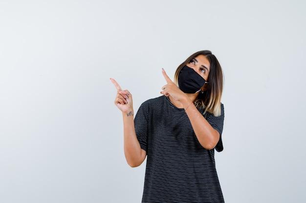 Jeune femme en robe noire, masque noir pointant vers le haut à gauche avec l'index et à la recherche focalisée, vue de face.