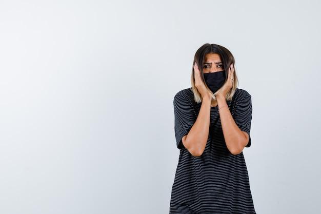 Jeune femme en robe noire, masque noir tenant les mains sur les joues et à la vue de face focalisée.