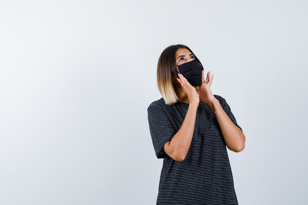 Jeune femme en robe noire, masque noir tenant par la main près de la bouche pour appeler quelqu'un et à la recherche focalisée, vue de face.
