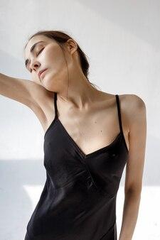 Jeune femme en robe noire pose