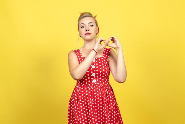 Jeune femme en robe à pois rouge posant sur jaune