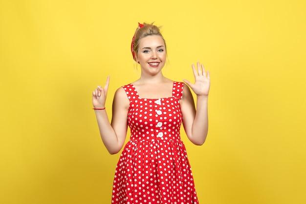 Jeune femme en robe à pois rouge souriant sur jaune
