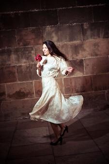 Jeune femme en robe qui danse dans la rue